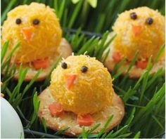 cheese balls on Ritz cracker, rolll in finely shredded cheddar cheese decorate with carrot pieces