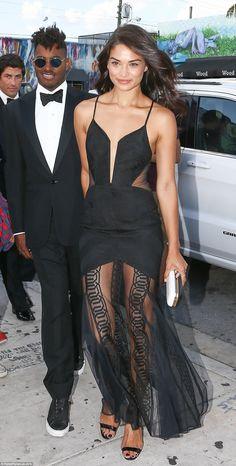 Model Shanina Shaik wore a slashed front black dress with a sheer mesh skirt...