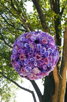 Pomanders of roses in shades of purple and pink hang from the trees.