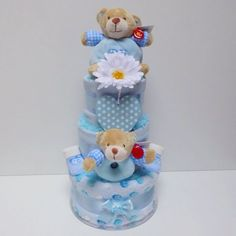 Our Deluxe 3 Tier Baby Boy #nappycake includes the following:  3 Tiers of Premium Branded Size 3 Nappies (4-9kgs/9-20lbs) 1 Soft Fleece Spotted Blanket 2 Quality Muslin Squares 1 Cute '1st Bear' Teddy by Keel Toys 1 Cute '1st Bear' Soft Rattle by Keel Toys 1 Gorgeous Wooden 'It's A Boy' Hanging Spotted Heart Plaque 1 Bodysuit 1 Bib 1 Pair of Socks 1 Super Soft Baby's Microfibre Face Towel 1 re-useable Cake Board. www.cheshirenappycakes.co.uk #baby #babygift #babyshower #gift