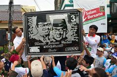 Warga Kampung Tanah Hadiahkan Karikatur Anies-Sandi Berupa Susunan Koin