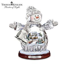 Thomas Kinkade Illuminated Crystal Snow Girl Figurine.  Limited-edition genuine crystal snow girl figurine with silvery accents holds an illuminated sculptural Thomas Kinkade Christmas village scene inside. #DeckTheHalls