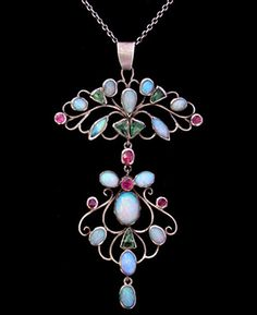 This is not contemporary - image from a gallery of vintage and/or antique objects. ARTHUR (1862-1928) & GEORGINA GASKIN (1866-1934)  A delicate Arts & Crafts silver pendant set with opals, rubies and emeralds and  with an opal drop.