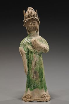 """Tang Dynasty Green Glazed Pottery Figure. Very unusual Chinese Tang Dynasty parcel green glazed pottery tomb figure; standing in long robes and wearing a crown with left hand up to her chest, elaborate details to her face and crown; H: 12"""""""