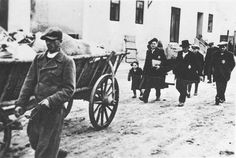 Jews walking next to carts loaded with their personal effects, being deported from Slovakia, 1942.