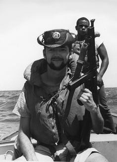 """Members of the """"Junk Force"""", 1967. Starting in 1963-64, American advisors were seconded to the Republic of Vietnam's Navy, with the task of performing interdiction on suspected Viet Cong smugglers. They became famous for unconventional tactics and motley uniforms, seen here with civilian clothing and a Thompson submachine gun."""