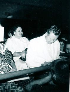 Elvis Presley's parents, Gladys and Vernon, are pictured on the set of Elvis's second movie LOVING YOU in February 1957. Vernon is signing an autograph.