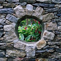 Test Garden Tip: If you're not lucky enough to have a granite wall like this, you can still create the same effect by cutting and framing a hole in a privacy fence. Or, if you don't have a great view beyond, fix a mirror to your fence and frame it with vines to give the illusion of a portal.