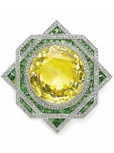A BELLE EPOQUE YELLOW SAPPHIRE, DIAMOND AND DEMANTOID GARNET PENDANT BROOCH, CIRCA 1915. Set with a circular-cut yellow sapphire, trimmed with rose-cut diamonds, within a calibré-cut demantoid garnet and rose-cut diamond overlapping surround, mounted in platinum and gold. #BelleÉpoque #brooch