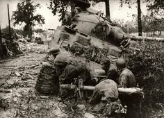Fallschirmjäger armed with Panzerfaust and Panzerschreck hiding behind a Sherman American Medium Tank after knocking it out, as another Sherman approaches the area.