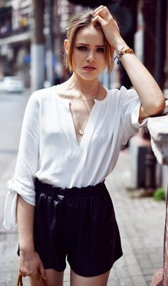 Kristina Bazan is wearing a white top and black short shorts from Zara