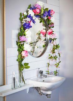 Aufnahme einer Blumengirlande aus SMYCKA Kunstblumen, hier Pfingstrosen in verschiedenen Farben, rund um einen Badezimmerspiegel arrangiert.