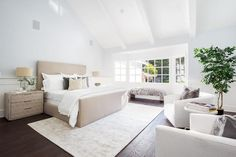 Under a white vaulted ceiling, this spacious bedroom features a light taupe bed accented with white hotel bedding and placed on a cream rug between light taupe 3 drawer nightstands lit by nickel lamps.