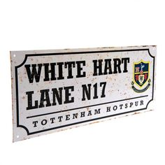 A metal street sign bearing the letters 'WHITE HART LANE N17' and a retro Tottenham Hotspur logo.