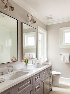 White and gray bathroom features a gray double washstand fitted with his and hers sinks and modern faucets and metal framed mirrors illuminated by Boston Functional Library Wall Lights.