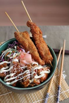Japanese Style Rice Dish topped with Chicken Teriyaki, Japanese Slaw and Tonkatsu on stick