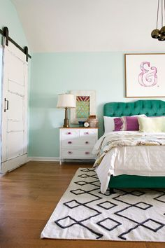 This master bedroom is the perfect get away from it all space. The colorful design includes a diamond tufted headboard in peacock blue and a side table with handmade knobs.