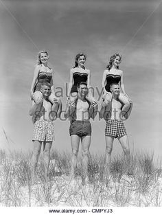 1950s 1960s THREE COUPLES AT BEACH ON DUNES WITH WOMEN IN IDENTICAL BATHING SUITS SITTING ON MEN'S SHOULDERS - Stock Image