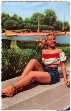 Bar shoulders, gold sandals, and flowing blonde locks add up to scads of appealing 1940s summertime style.