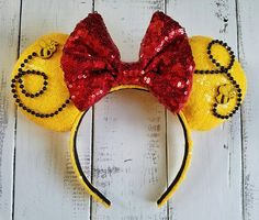 Inspired by Pooh Bear, these ears are handmade/individually made to order with golden yellow sequin fabric, red sequin bow, with bumble bee embellishments and beading Each piece is handmade and made to order. No two pieces are alike and subtle differences should be expected