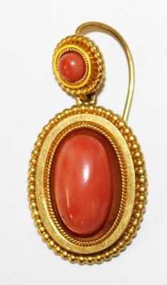 A Victorian coral earpendant.  with coral cabochon within beaded and ropetwist border