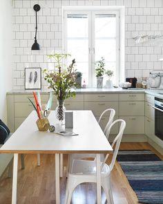 Lindblomsgrönt kök med ekgolv och vitt kakel