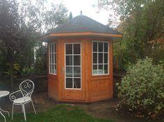 Kleiner Gartenpavillon aus lasiertem Holz.