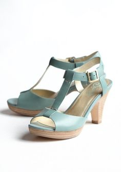 Effortlessly sophisticated, these leather seafoam heels feature a classic design with a stacked heel and an adjustable ankle strap.