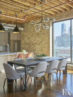 City loft dining room with exposed wooden beam ceilings and brick walls | Elizabeth Krueger Design