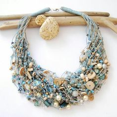 Floating necklace- perfect summer accessory. Sea blues, creams, wood, and beads.