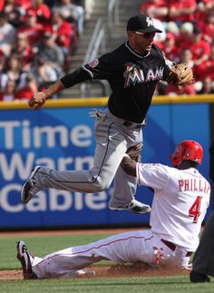 Cincinnati Reds' Brandon Phillips (4) is forced out at second base under Miami Marlins second baseman Omar Infante, left, during the first inning of the Reds' Opening Day baseball game, Thursday, April 5, 2012, in Cincinnati. (AP Photo/David Kohl)  DAVID KOHL / AP