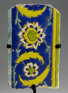 A Safavid cuerda seca border pottery Tile   Persia, 17th Century  decorated in yellow, green, turquoise and black outline on a blue ground, with meandering saz style vines and lotus flowers, mounted   22.8 cm. x 14 cm.