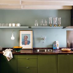 I'm really digging this kitchen color combo. The dark olive green cabinets really work with the sky blue walls. A full-on olive kitchen would be too heavy and dark, but the blue serves to lighten the look just enough. It's a little retro feeling, but just modern enough. What do you think?