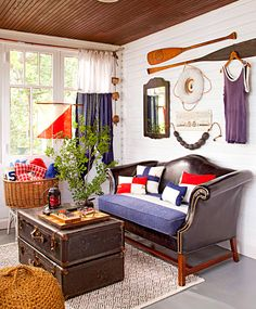 Huge ship signal flags become curtains and throw pillows while retired buoys and oars hang as wall art in this nautical-themed porch. More ideas for decorating with flea finds: http://www.midwestliving.com/homes/flea-bitten-3-flea-market-makeovers