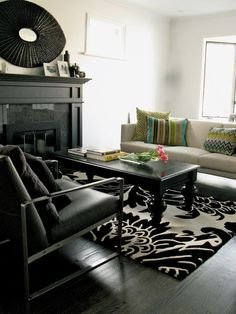 This space uses the high contrast of black floors and white walls to set up a dramatic look. Colorful cushions and a rug with an oversize floral print keep things feeling hip and fun rather than stark.