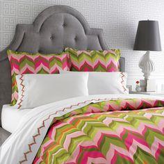 Bright bedding against a gray tufted headboard. leuke print voor in een kinderkamer.