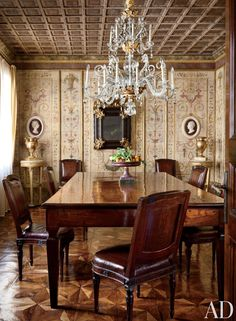 Traditional Dining Room of Villa Bucciol in Oderzo, near Venice. The walls are covered in hand-painted terra-cotta tiles, bordered by gilded wood. A late 18th-century chandelier adds to the room's grandeur as do the Neoclassical gilded gueridons at the corners. Designed by Studio Peregalli.
