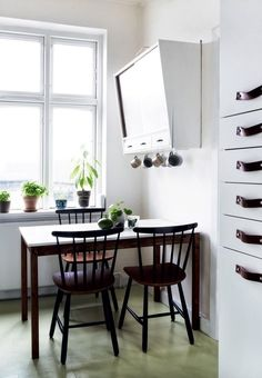 Small dining area in the kitchen with smart storage and green plants.