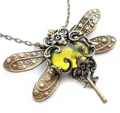 """This dragonfly necklace is artisan crafted using vintage style filigree. The dragonfly features on it's body an antique olive oil green glass cabochon jewel encased in a Victorian style filigree jewelry design. This beautiful dragonfly design is named """"Olive Divine"""""""