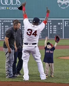 Big man, little man: Six-year-old Maverick Schutte of Cheyenne, Wyo., who has undergone more than 30 surgical procedures because of a congenital heart defect, celebrates with Boston Red Sox designated hitter David Ortiz after throwing out the ceremonial first pitch prior to a baseball game against the Oakland Athletics at Fenway Park in Boston, May 11. Ortiz fulfilled a promise to hit a home run just for Schutte in a recent game against the New York Yankees.