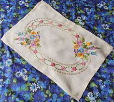 Beautiful hand embroidered linen tray cloth - used  I think this is from the 50s but I am not absolutely sure  Beautifully done embroidery on a ivory colour linen in such gorgeous colours - lavender, lilac, golden yellow, grass green, water green, mushroom, cream, sienna brown, pale mauve, dusty pink, sky blue and soft orange . The colour combination and craftsmanship are lovely.  Dimensions - approx. 19 x 13  Condition - This has been occasionally used over the years but is in beautiful…