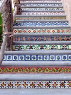 Once we take up the carpet I want to do something like this with either mexican tiles or cool wallpaper on the risers - hopefully we can leave the wood steps - maybe just get away with painting that part!