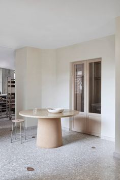The service area is anchored by a steel-framed wooden counter, atop of which is a glass box where bread loaves, buns and Danish pastries are displayed. Xiamen, Bakery Interior, Limestone Wall, Off White Walls, Interior Minimalista, Wooden Counter, Terrazzo Flooring, Oak Doors, Minimalist Interior