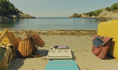 A cat in a basket on the beach, seen in a still from Moonrise Kingdom of Sam and Suzy's campsite, with a centrally placed portable record player (Credit: Wes Anderson)