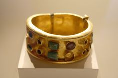 A Late Roman Gold Cuff Bracelet Inlaid with Glass and Precious Stones     Gold, glass, and precious stones (emeralds, sapphires, garnets), ca. 370-400 C.E.  Found together with the preceding coin belt and the following bracelet.  From the collection of the Getty Villa, Malibu, California.