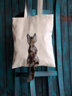 This tote bag is fun and practical and makes the perfect gift for a cat lover. Featuring a faux fur cat, this 100% cotton canvas tote in natural creamy white color is strong enough to carry books, groceries or personal effects. It has long handles, to carry over your shoulder. The best way to go shopping or to the beach with lots of things on it. The bag is big enough to wear all your things: the wallet, mobile, tablet or even laptop, your diary, some books or clothes. It has three large…