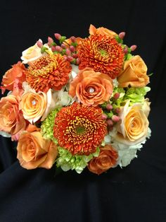 Bouquet of orange, green and white flowers including hydrangea, roses, hypericum and geranto gerbs.