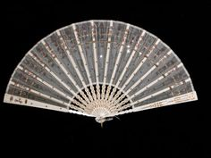 1800 Battoir fan: ivory silk gauze mounted on ivory painted wooden sticks, pinned with loop at one end. Decorated with sequins, repeated at each. National Trust