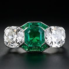 One of the greatest Art Deco Three-Stone rings ever! At arms length, a rich green old mine Colombian emerald looks to be about 4.00 carats (if you include the calibre emeralds embracing it top and bottom!), but it actually weighs 1.50 carats. The bright green gem is embraced left and right by a gorgeous, bright-white pair of antique cushion-cut diamonds weighing 4.00 carats total, all adding up to a truly stunning showstopper of an original Art Deco ring, circa 1925.