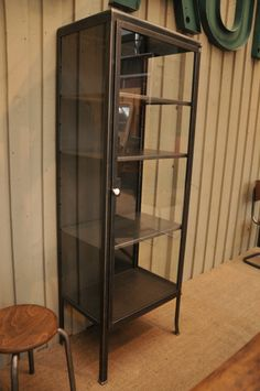 French industrial metal glazed bookcase c. 1940 with three shelves and a white ceramic handle. Would also make a great bathroom cabinet.